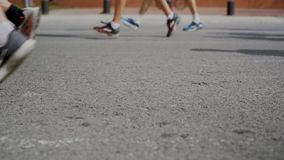 Marathon runners unrecognizable on city street. Slow motion close up shot of marathon runners in athletic gear sneakers pass by on fast pace during competition stock footage