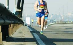 Marathon running in the morning light . Running on city road. Athlete runner feet running. Young runners running on city bridge stock photos