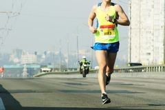 Marathon running in the morning light . Running on city road. Athlete runner feet running. Young woman runner running on city stock photo