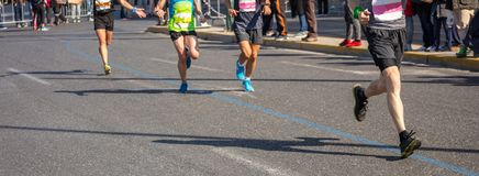 Marathon running race, runners running on city roads, detail on legs. Marathon running race, group of runners on city roads, detail on legs, banner stock image