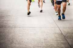Marathon running race people competing in fitness and healthy ac. Tive lifestyle feet on road stock images