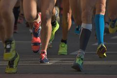 Marathon running race people competing. In fitness and healthy active lifestyle feet on road stock photos
