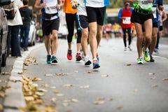 Marathon running race, people feet. On autumn road Royalty Free Stock Image
