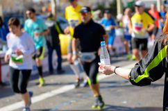 Marathon running race, runners on road, refreshment point. Marathon running race, runners on road, volunteer giving water on refreshment point Royalty Free Stock Images