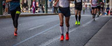 Marathon running race, runners running on city roads, detail on legs. Marathon running race, group of runners on city roads, banner, detail on legs royalty free stock images
