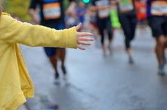 Marathon running race,runners support on road race, child`s hand giving highfive, kid supporting athletes who run stock photos