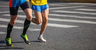 Marathon running race, two men runners on city roads, detail on legs. Copy space royalty free stock photos
