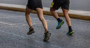 Marathon running race, two runners on city roads, detail on legs. Marathon running race, two men runners on city roads, detail on legs stock images