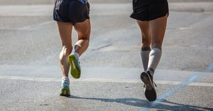 Marathon running race, two runners on city roads, detail on legs. Back view stock photos