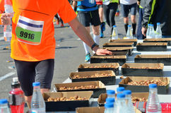 Marathon running road race, runners hand taking food and drinks on refreshment point, sport, fitness and healthy lifestyle. Concept royalty free stock photo