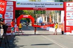 Marathon winner woman at finish. Happy marathon runner finish line. ODESSA, UKRAINE - 25 JUN 2017: Excited female runner crossing the finshline of a marathon Stock Photography