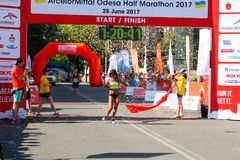 Marathon winner woman at finish. Happy marathon runner finish line. ODESSA, UKRAINE - 25 JUN 2017: Excited female runner crossing the finshline of a marathon Stock Image