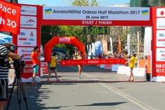 Marathon winner woman at finish. Happy marathon runner finish line. ODESSA, UKRAINE - 25 JUN 2017: Excited female runner crossing the finshline of a marathon Royalty Free Stock Photos