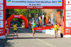 Marathon winner woman at finish. Happy marathon runner finish line. ODESSA, UKRAINE - 25 JUN 2017: Excited female runner crossing the finshline of a marathon Royalty Free Stock Photo