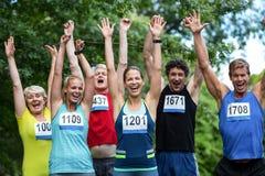 Marathonathleten, die mit den angehobenen Armen aufwerfen lizenzfreie stockbilder