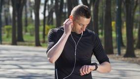 Marathoner, der Musik hört und in den tragenden Kopfhörern des Parks ausbildet und stoppt, um smartwatch Verfolger zu überprüfen stock video footage
