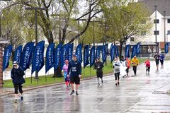 Marathoners running in cold rainy wet conditions, stock image