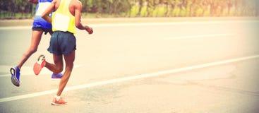 Marathoniens fonctionnant sur la route urbaine Image stock