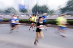 Marathonläufer, die auf der Straße laufen Stockfotos