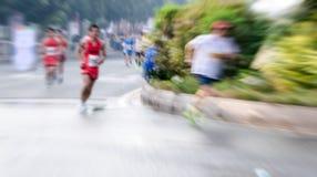 Marathonläufer, die auf der Straße laufen Stockbilder