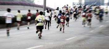 Marathonläufer, die auf der Straße laufen Stockfotografie
