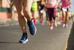 Marathonläufer, die auf Stadtstraße laufen Stockbilder