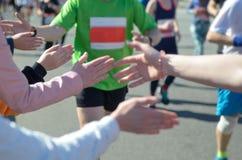 Marathonlaufenrennen, Stütz-Läufer auf Straße, Kind-` s Hand highfive, Sportkonzept Stockbilder