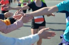 Marathonlaufenrennen, Stütz-Läufer auf Straße, Kind-` s Hand highfive, Sportkonzept Stockbild