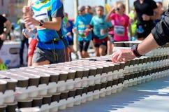Maratońska bieg rasa, biegacze na drodze, izotoniczni napoje na orzeźwienie punkcie fotografia stock