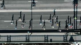 Maratona da corrida da multidão dos desportistas ao longo da estrada cinzenta sem tráfego vídeos de arquivo