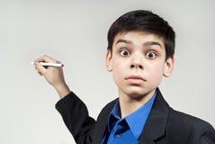 A maravilha do menino olha com uma pena de ballpoint fotos de stock