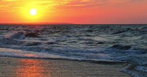 Maravillosamente ondas de balanceo en los rayos de la puesta del sol del sol almacen de video