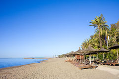 Marbella Beach. Sun loungers on a sandy beach by the Mediterranean Sea at the popular resort of Marbella in southern Spain, Costa del Sol, Andalusia region Stock Photo
