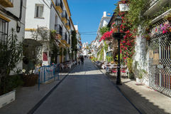 Marbella street with church in the background. And traditional spanish architecture with flowers Stock Image