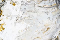 Marble background texture with gold, black, grey and white colors, using acrylic pouring medium art technique. Useful as a. Backdrop or background, or copy stock image