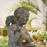Marble baroque statue detail, boy statue in a garden. Stock Photo