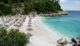 Marble beach - Saliara beach, Thassos Island, Greece. Tourists enjoying a nice summer day at the Marble beach in Thassos Island. There are umbrellas and sunbeds Royalty Free Stock Photo
