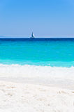 Marble beach and turquoise water with sailboat on horizon, Thassos island Stock Photos