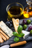 Marble board with cheese selection, wine and grapes Royalty Free Stock Images
