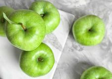 Marble board with fresh green apples on table,. Top view Royalty Free Stock Images