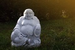Marble budai hotei in a garden- is a Chinese folkloric deity. Name means `Cloth Sack`, a laughing buddha. Note to the reviewer: royalty free stock images