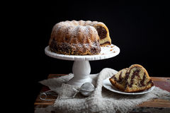 Marble bundt cake. On wooden table, black background Royalty Free Stock Images