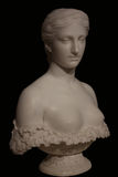 Marble bust of beautiful woman. Marble bust of a beautiful young woman baring her breasts isolated on a black background. Taken at the Milwaukee Museum of Art Royalty Free Stock Photo