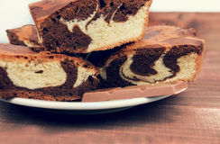 Marble cake in white plate cut into pieces a la carte. Standing next to a cup of hot chocolate and milk chocolate tile pieces on a wooden table in the rural Royalty Free Stock Photo