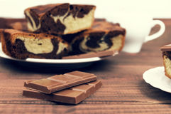Marble cake in white plate cut into pieces a la carte. Standing next to a cup of hot chocolate and milk chocolate tile pieces on a wooden table in the rural Royalty Free Stock Images