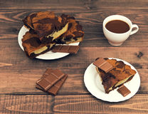 Marble cake in white plate cut into pieces a la carte. Standing next to a cup of hot chocolate and milk chocolate tile pieces on a wooden table in the rural Stock Photos