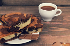 Marble cake in white plate cut into pieces a la carte. Standing next to a cup of hot chocolate and milk chocolate tile pieces on a wooden table in the rural Stock Images