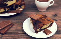 Marble cake in white plate cut into pieces a la carte. Standing next to a cup of hot chocolate and milk chocolate tile pieces on a wooden table in the rural Royalty Free Stock Image