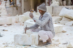 Marble carvers In Rajasthan. Rajasthan, India, 21st January 2017 - Artisans carving Hindu gods and  saints from white marble Royalty Free Stock Photography