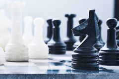 Marble chess on a chess Board. A marble chess set on a chess Board royalty free stock image